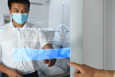 """A man clicks the mirror to check his healthy status in the Chongqing Lijia Smart Park, where people can experience """"A Day of The Smart Life"""", as part of the exhibitions of Smart China Expo 2021. (Photo by Chen Chao/ China News Service)"""